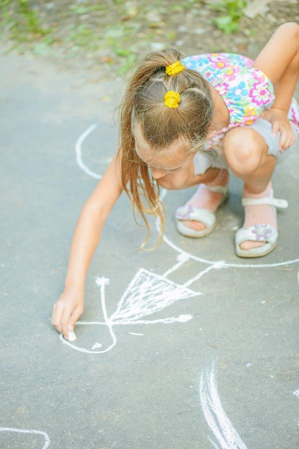 La petite fille dessine avec la craie photographie stock