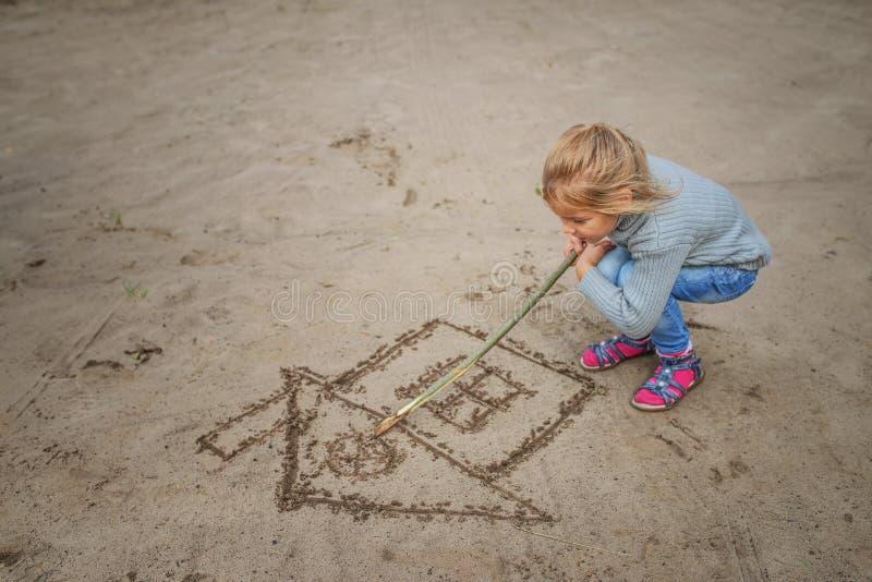 La petite fille dessine dans le sable photo stock