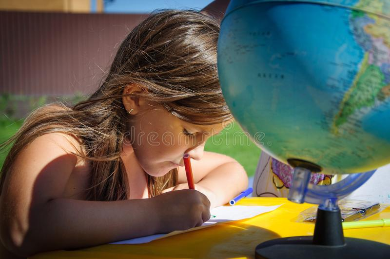 La petite fille dessine des marqueurs dehors en été photos stock