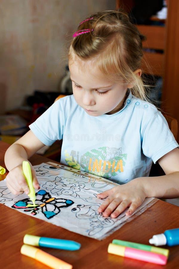 La petite fille dessine les couleurs en verre souillé de l'enfant photo libre de droits