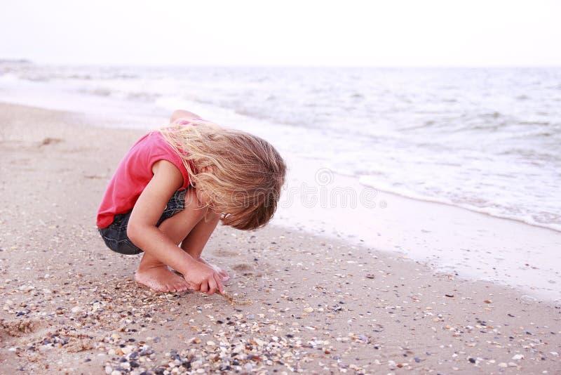 La petite fille dessine un soleil dans le sable sur le bord de la mer images libres de droits