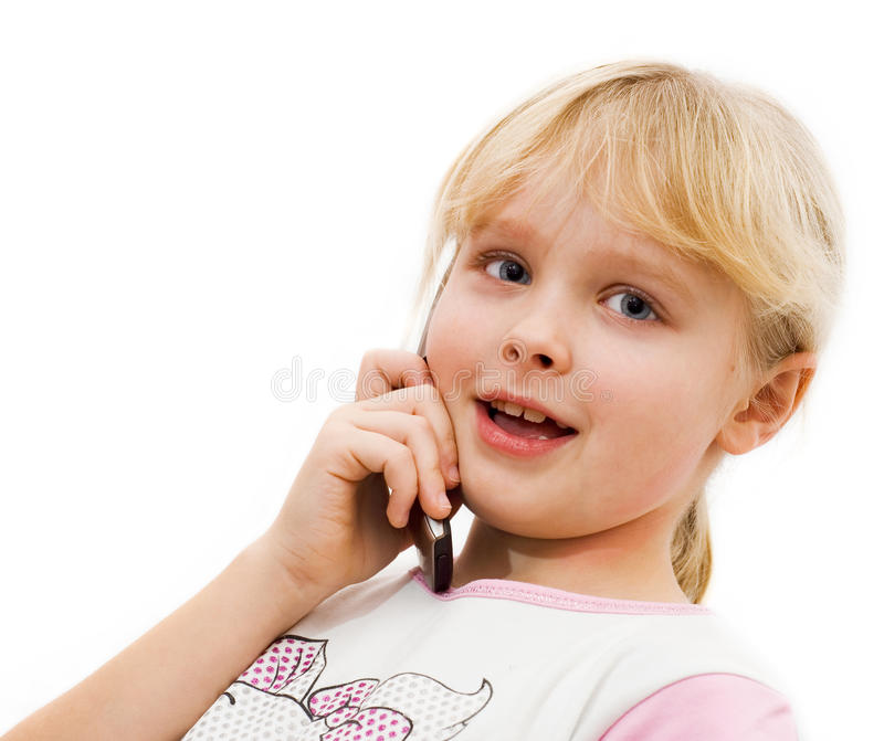 La petite fille dit sur un téléphone portable photos libres de droits