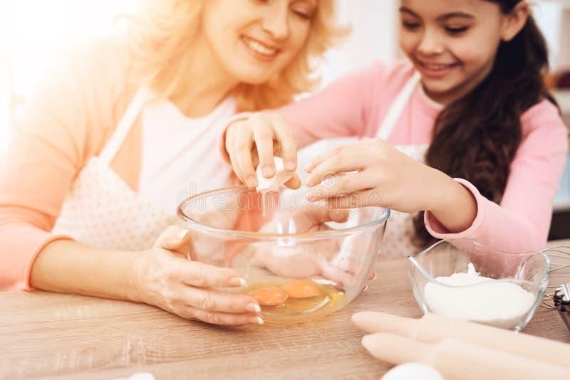 La petite fille divise l'oeuf en cuvette, se reposant avec sa grand-mère dans la cuisine images libres de droits