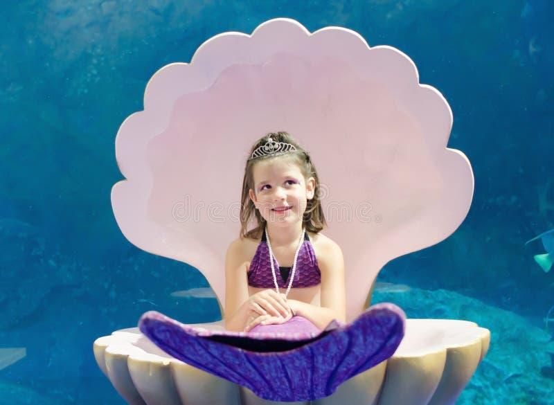 La petite fille douce s'est habillée dans le séjour de costume de sirène dans la grande coquille o images libres de droits