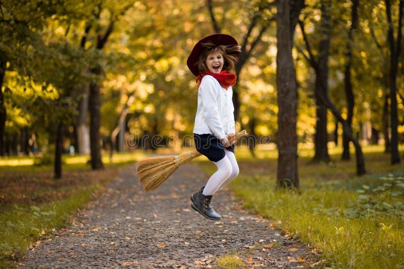 La petite fille drôle vole sur le balai en automne photos stock
