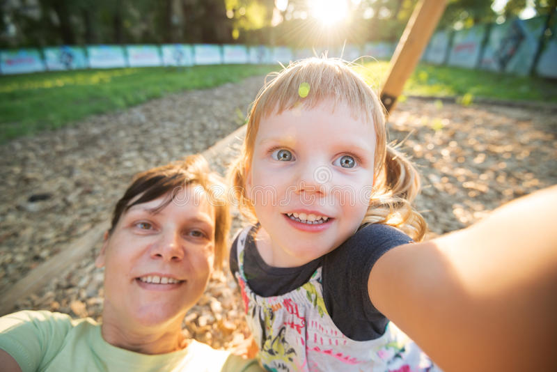 La petite fille drôle avec sa mère heureuse prennent le selfie images stock
