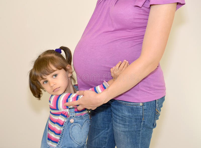 La petite fille embrasse la mère enceinte de mains photo libre de droits