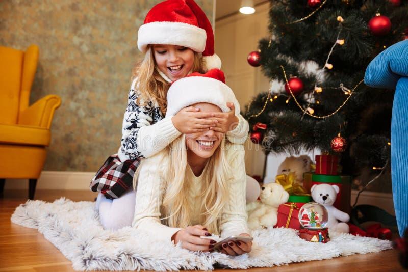 La petite fille espiègle dans le chapeau du ` s de Santa couvrant ses mères observe dedans photo libre de droits