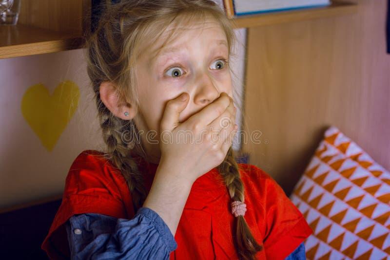 la petite fille est effrayée regardant une TV image stock