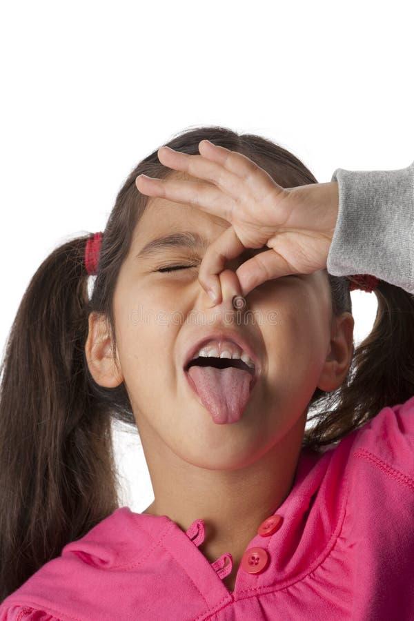 La petite fille est fermante son nez avec he2090909-086 image libre de droits