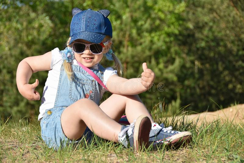 La petite fille est jouante et riante sur la pelouse verte en été photo stock