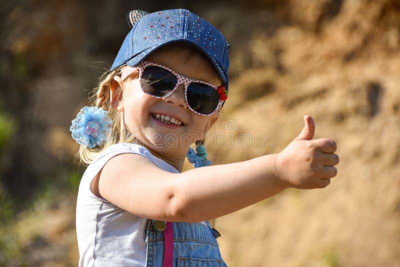 La petite fille est jouante et riante sur la pelouse verte en été photographie stock