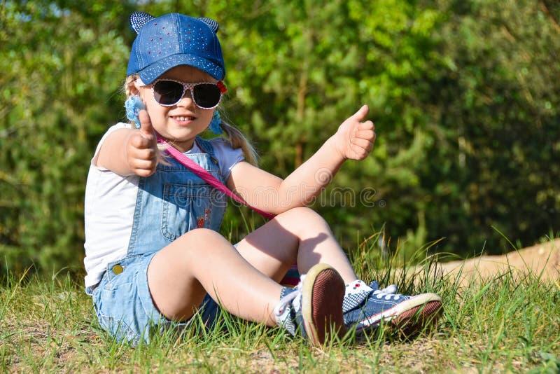 La petite fille est jouante et riante sur la pelouse verte en été photos stock