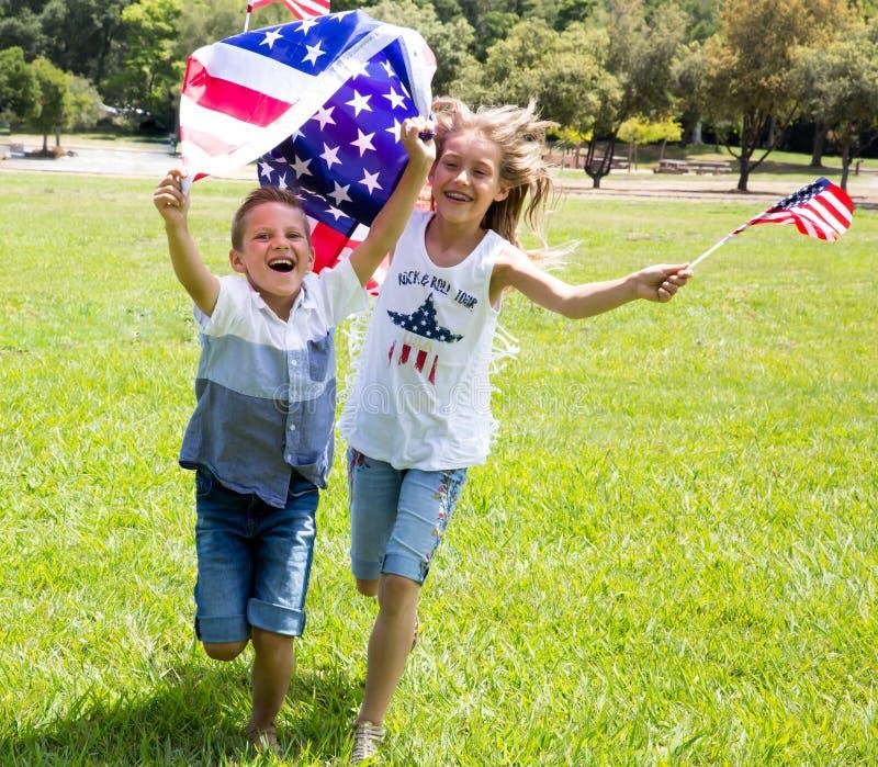 La petite fille et le garçon adorables courent sur l'herbe vert clair tenant le drapeau américain dehors le beau jour d'été photographie stock