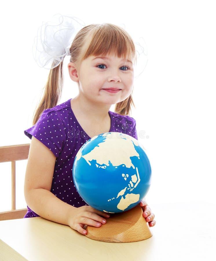 La petite fille examine le globe images stock