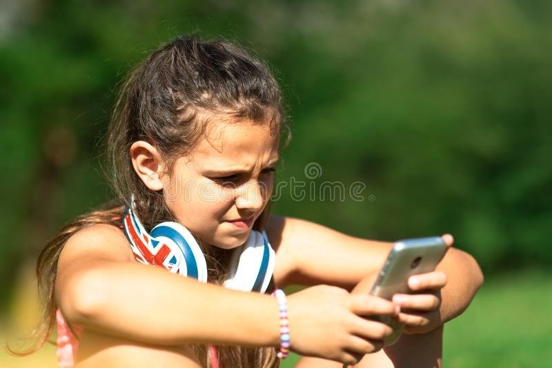 La petite fille explore les réseaux sociaux avec son smartphone photographie stock