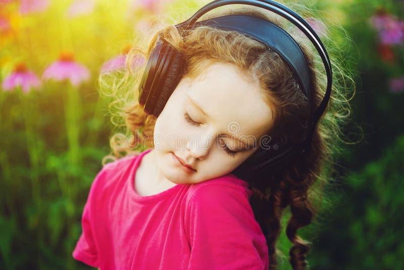 La petite fille a fermé ses yeux et écoute la musique sur des écouteurs dedans image stock