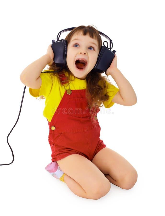 La petite fille gaie chante la musique image stock