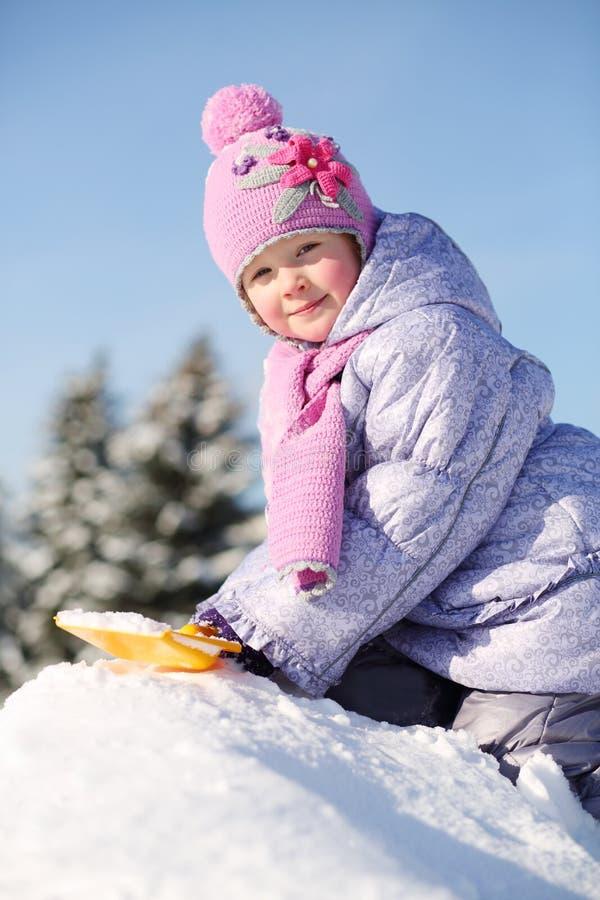 La petite fille habillée dans des vêtements chauds avec la pelle s'assied sur la pile image stock