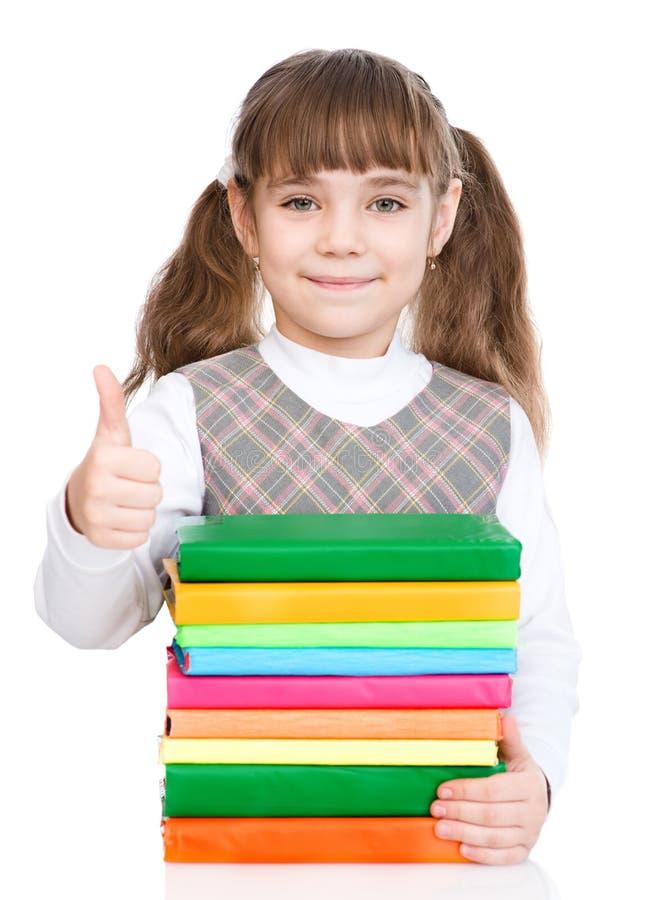 La petite fille heureuse avec la pile réserve montrer des pouces  D'isolement photo libre de droits