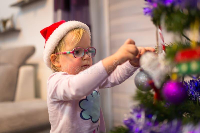 La petite fille heureuse décorent l'arbre de Noël photo libre de droits