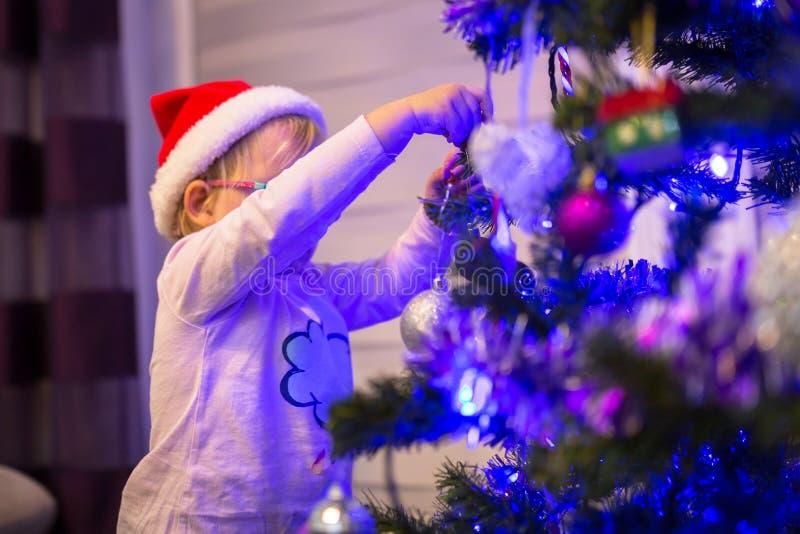 La petite fille heureuse décorent l'arbre de Noël image stock