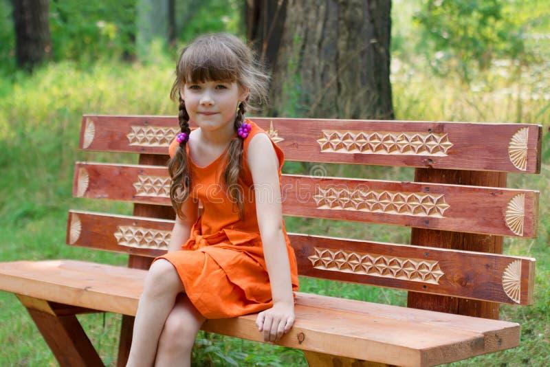La petite fille heureuse dans l'orange s'assied sur le beanch en bois à l'été image stock