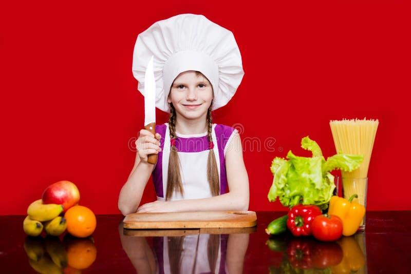 La petite fille heureuse dans l'uniforme de chef coupe le fruit dans la cuisine Chef d'enfant Cuisson du concept image stock