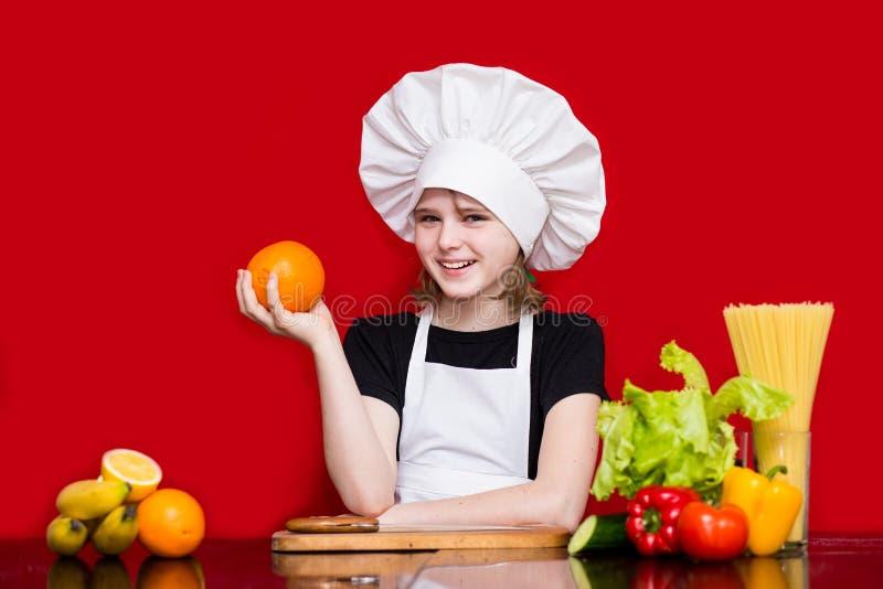 La petite fille heureuse dans l'uniforme de chef coupe le fruit dans la cuisine Chef d'enfant Procédé de cuisson photos stock