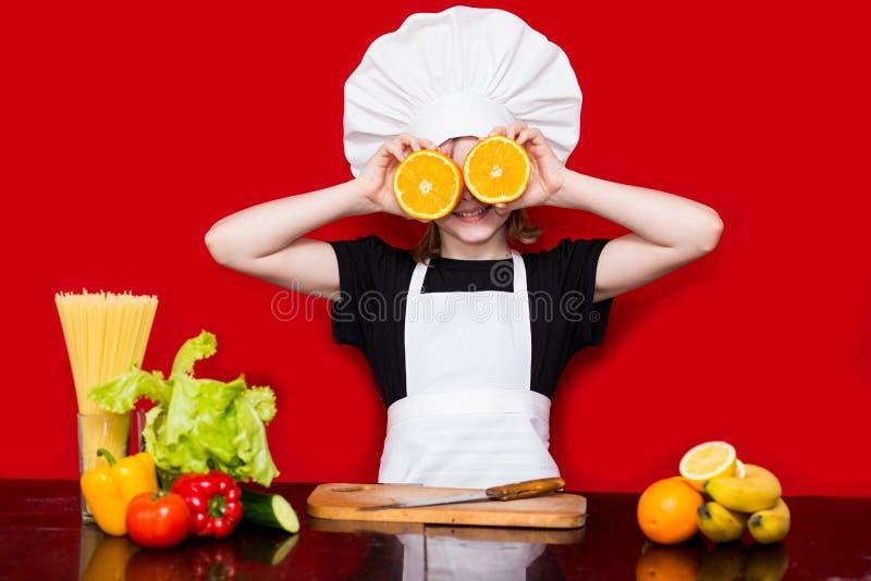 La petite fille heureuse dans l'uniforme de chef coupe le fruit dans la cuisine Chef d'enfant Procédé de cuisson images libres de droits