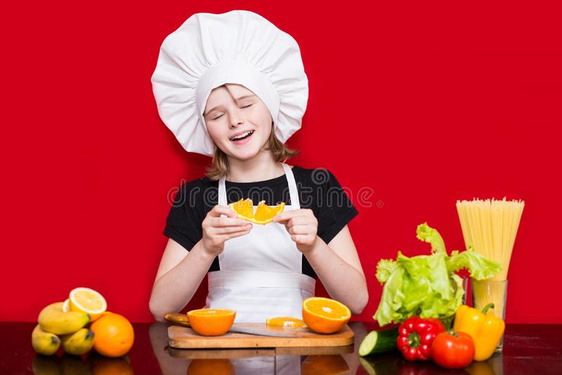 La petite fille heureuse dans l'uniforme de chef coupe le fruit dans la cuisine Chef d'enfant Procédé de cuisson photographie stock libre de droits
