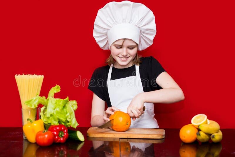La petite fille heureuse dans l'uniforme de chef coupe le fruit dans la cuisine Chef d'enfant Procédé de cuisson photographie stock