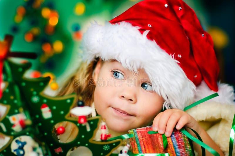 La petite fille heureuse dans le chapeau de Santa a Noël photo stock
