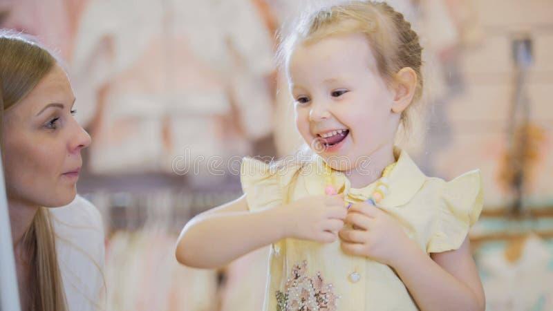 La petite fille heureuse essaye la chemise d'été dans le magasin photo libre de droits