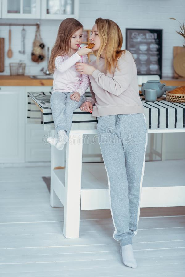 La petite fille heureuse et sa belle jeune mère prennent le petit déjeuner ensemble dans une cuisine blanche Ils boivent du lait  photos libres de droits