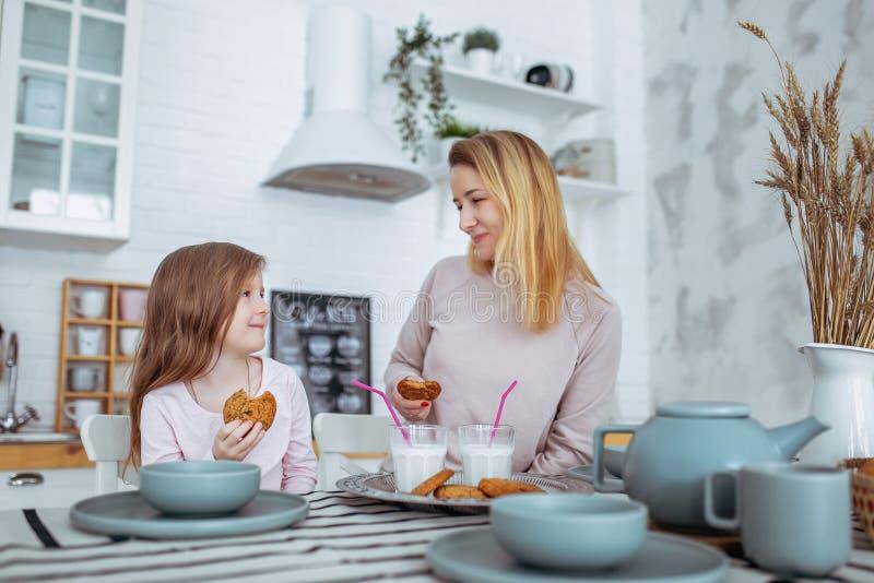 La petite fille heureuse et sa belle jeune mère prennent le petit déjeuner ensemble dans une cuisine blanche Ils boivent du lait  photographie stock libre de droits