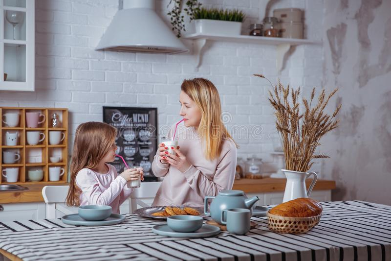 La petite fille heureuse et sa belle jeune mère prennent le petit déjeuner ensemble dans une cuisine blanche Ils boivent du lait  photo stock