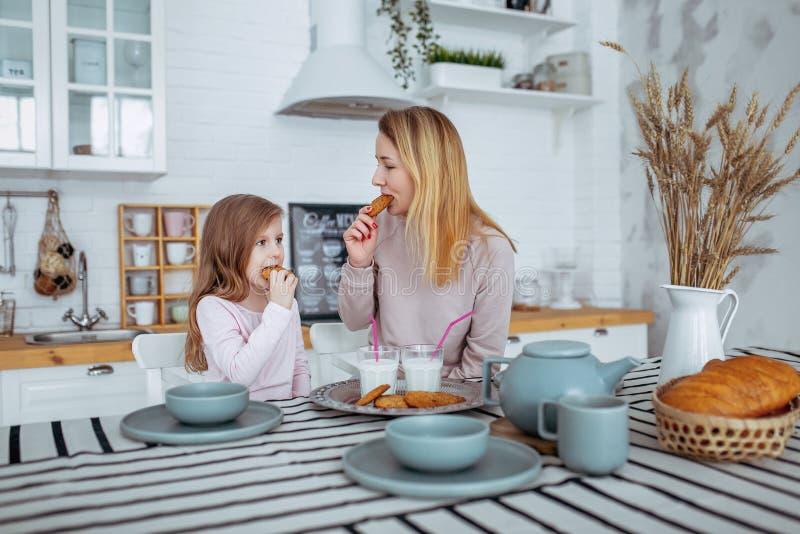 La petite fille heureuse et sa belle jeune mère prennent le petit déjeuner ensemble dans une cuisine blanche Ils boivent du lait  images libres de droits