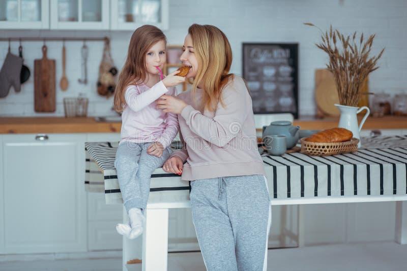 La petite fille heureuse et sa belle jeune mère prennent le petit déjeuner ensemble dans une cuisine blanche Ils boivent du lait  photo libre de droits