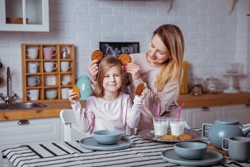 La petite fille heureuse et sa belle jeune mère prennent le petit déjeuner ensemble dans une cuisine blanche Ils ont l'amusement  images stock