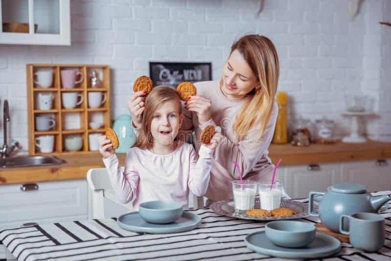 La petite fille heureuse et sa belle jeune mère prennent le petit déjeuner ensemble dans une cuisine blanche Ils ont l'amusement  photo stock
