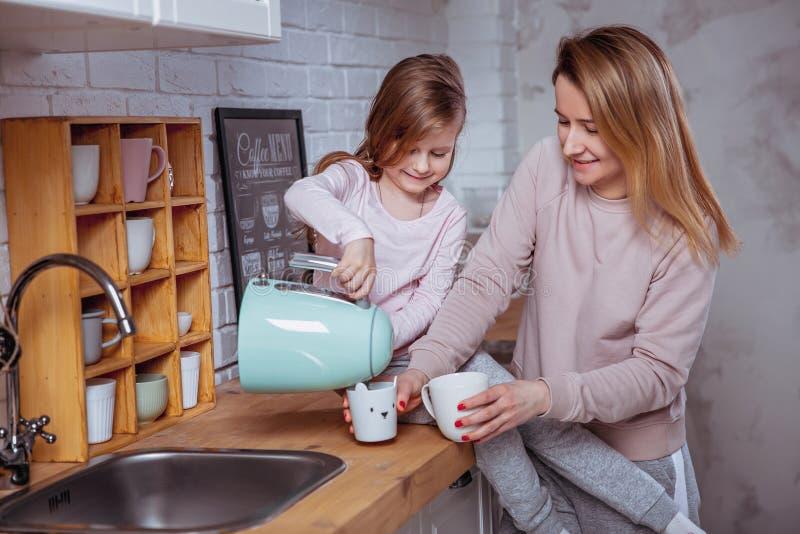La petite fille heureuse et sa belle jeune mère prennent le petit déjeuner ensemble dans une cuisine blanche Ils versent et boive images stock