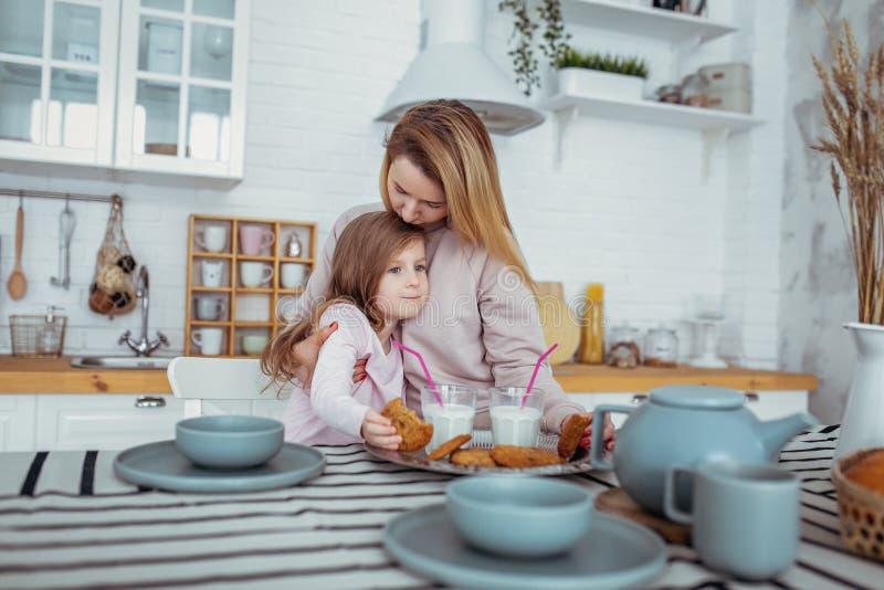 La petite fille heureuse et sa belle jeune mère prennent le petit déjeuner ensemble dans une cuisine blanche La maman étreint et  photos libres de droits
