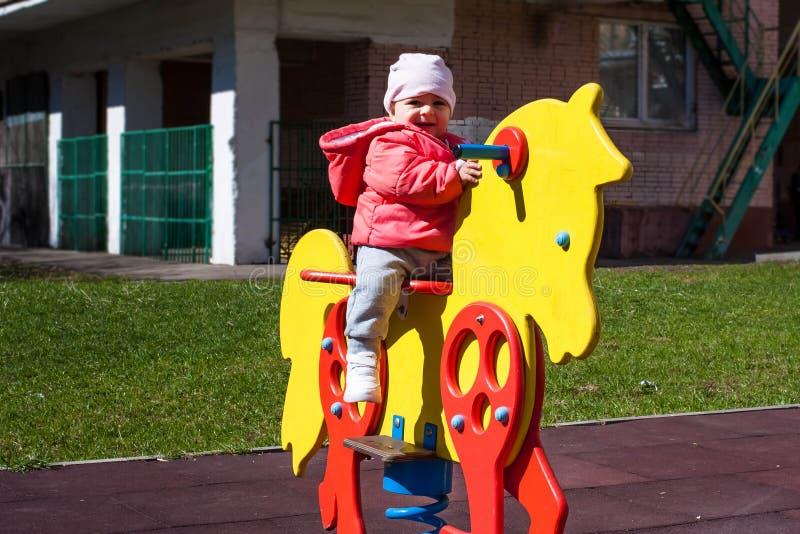 La petite fille heureuse habillée dans une veste rose s'assied sur un cheval jaune de jouet Les jeux de bébé sur le terrain de je image libre de droits