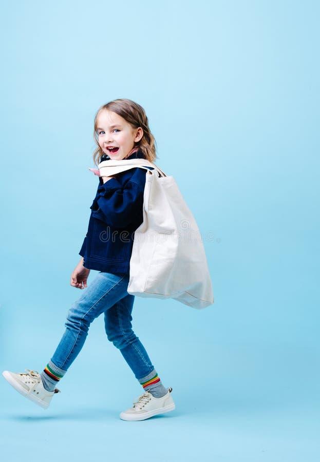 La petite fille heureuse marche le long, tenant le sac d'eco images stock