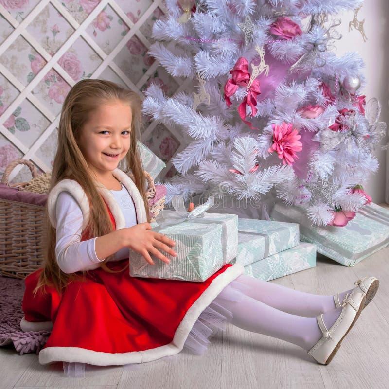 La petite fille heureuse ouvre des cadeaux de Noël images libres de droits