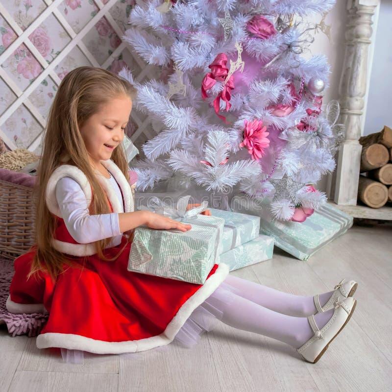La petite fille heureuse ouvre des cadeaux de Noël photographie stock libre de droits