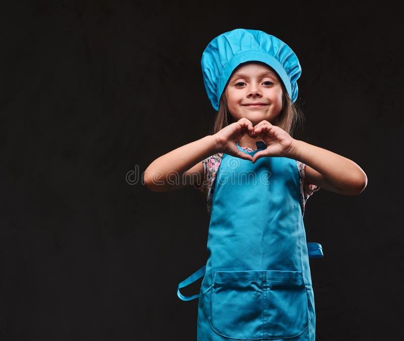 La petite fille heureuse s'est habillée dans le geste uniforme d'amour d'expositions de cuisinier bleu sur un fond texturisé fonc image libre de droits