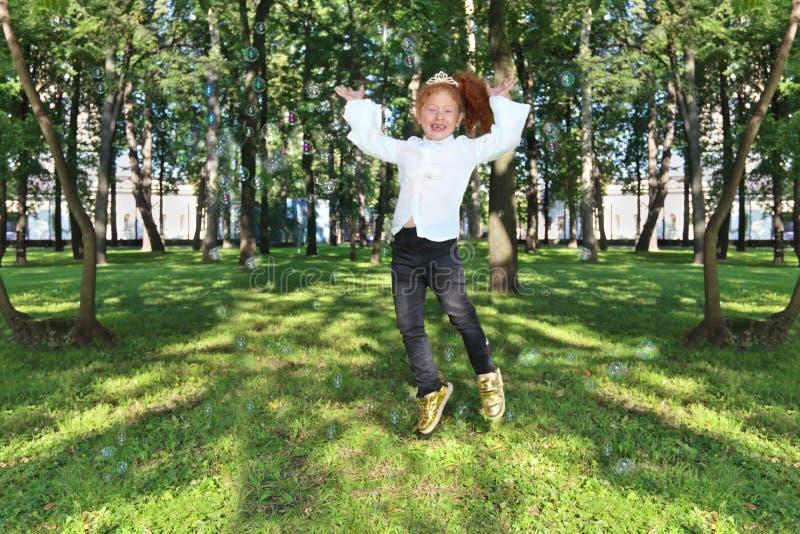 La petite fille heureuse saute parmi des bulles de savon photo libre de droits