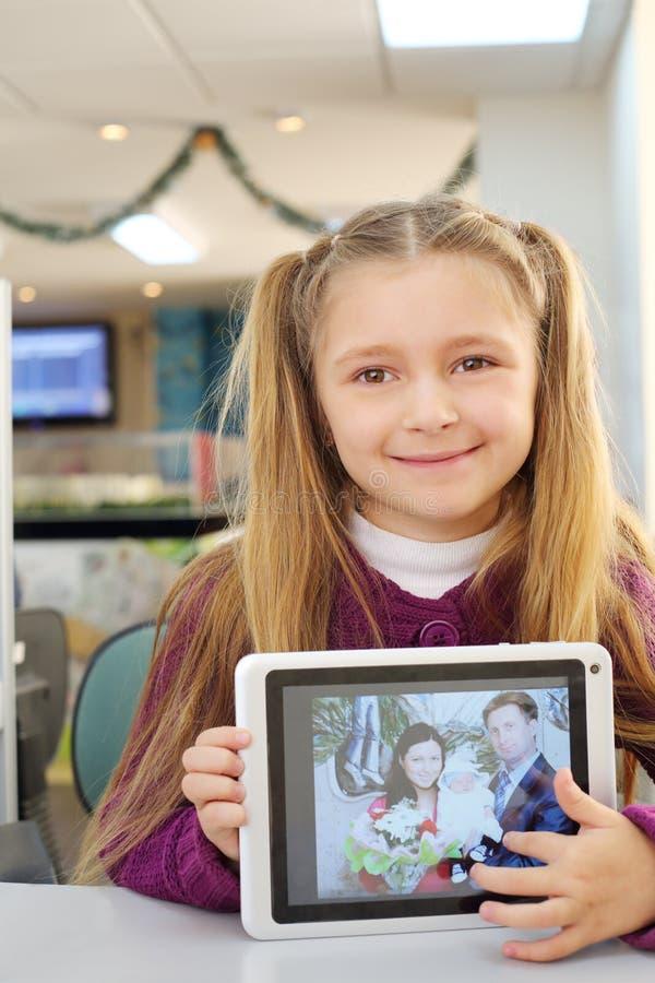 La petite fille heureuse tient la tablette avec la photo de sa famille image stock